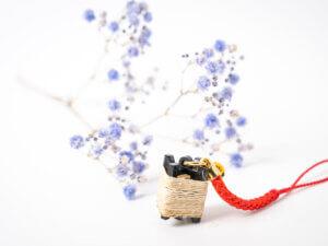昭和村産の苧を手で績んだ糸を生産用具の糸紡ぎ枠のミニチュアに巻きました。